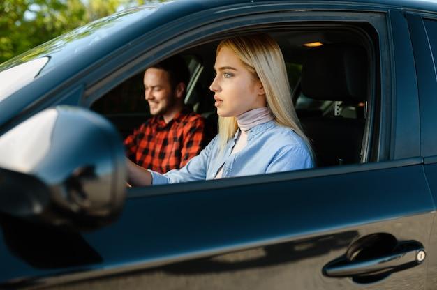 Studentin und ausbilderin im auto, fahrschule. mann, der eine frau lehrt, fahrzeug zu fahren. führerscheinausbildung