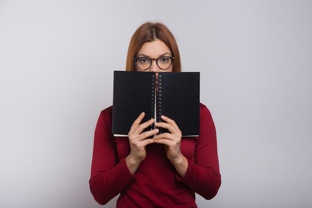 Studentin versteckt sich hinter notizbuch