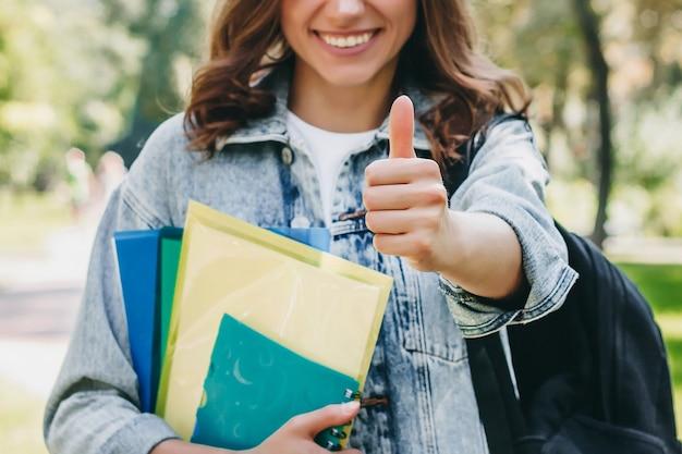 Studentin zeigt geste wie im park