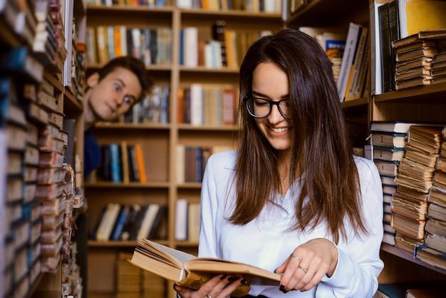 Studentinnen, die ein buch in der bibliothek lesen, und ein anderer verliebter männlicher student, der sie ausspioniert