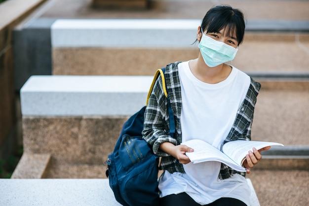 Studentinnen, die masken und bücher auf der treppe tragen.