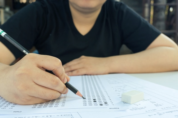 Studentinnen hand mit bleistift schreiben ausgewählte wahl auf antwortblättern und mathematik-fragebögen. studenten, die prüfung machen. schulprüfung
