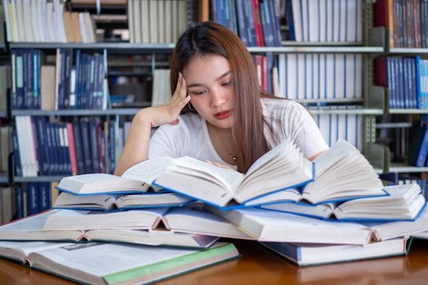 Studentinnen sind gestresst, wenn sie viele bücher lesen, die auf den tischen in der bibliothek stehen. vorbereitung auf die prüfung