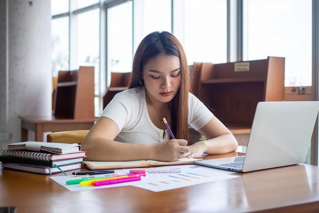 Studentinnen sitzen und machen hausaufgaben machen sie sich notizen, machen sie berichte in der bibliothek.
