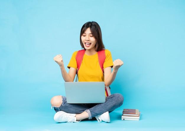 Studentinnenportrait auf blauem hintergrund sitzend ná» n