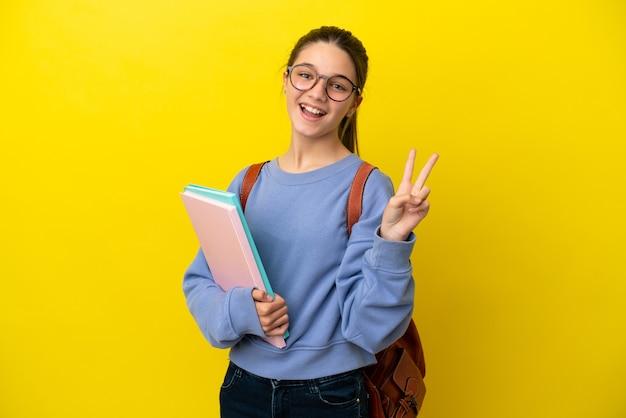 Studentische kinderfrau über isoliertem gelbem hintergrund, die lächelt und victory-zeichen zeigt