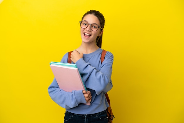 Studentische kinderfrau über isolierter gelber wand, die einen sieg feiert