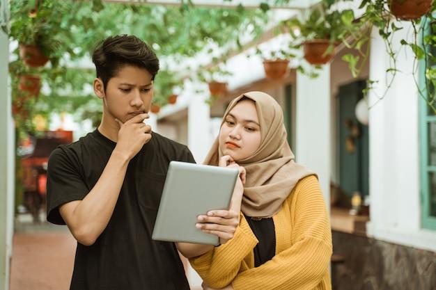 Studentische männer und hijab-mädchen sorgen sich, wenn sie auf den bildschirm des tablets schauen