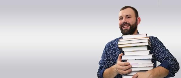 Studentischer erwachsener bartmann mit buchstapel in einer bibliothek