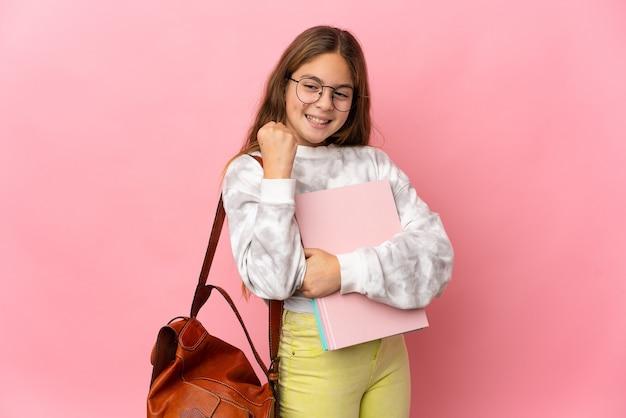 Studentisches kleines mädchen über isoliertem rosa hintergrund, der einen sieg feiert