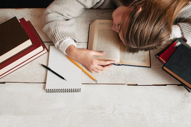 Studentisches mädchen, das auf schreibtisch mit büchern schläft