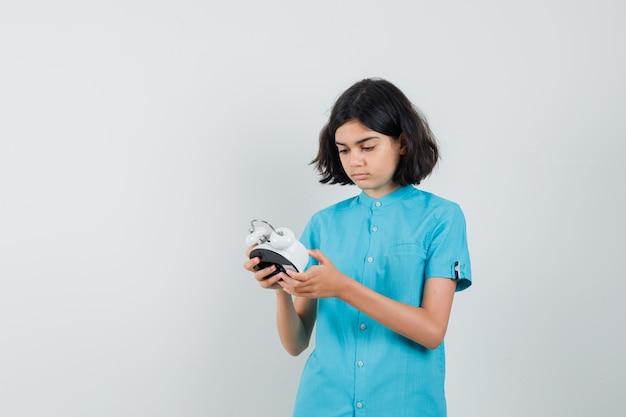 Studentisches mädchen, das uhr im blauen hemd betrachtet und aufmerksam schaut.