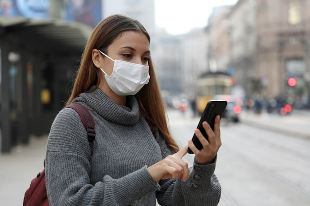 Studentisches teenager-mädchen mit schutzmaske, die für online-transportticket zahlt