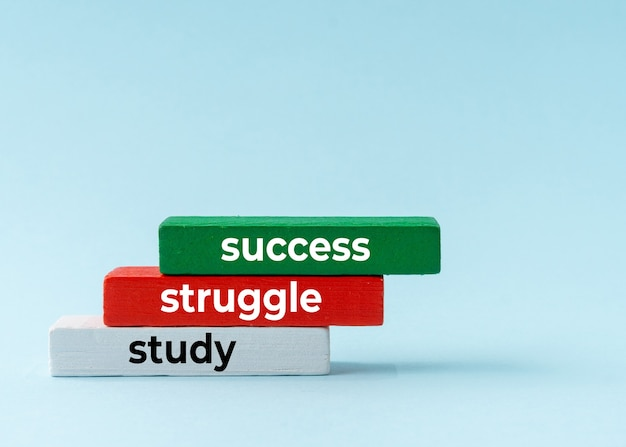 Studien-, kampf- und erfolgskonzept auf buntem holzblock.