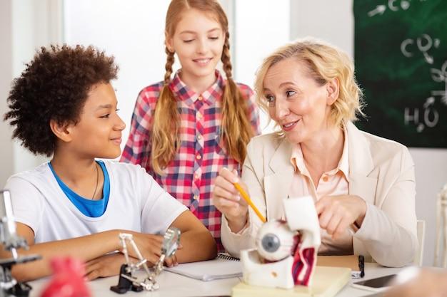 Studienprozess. freudige positive lehrerin, die ihren schüler ansieht und ihm das material erklärt