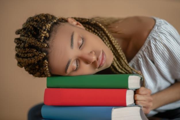 Studienprozess. müde junge afroamerikanische frau, die auf stapel bücher schläft