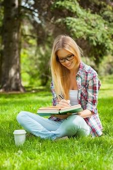 Studieren im freien. selbstbewusste junge studentin, die beim sitzen in einem park studiert