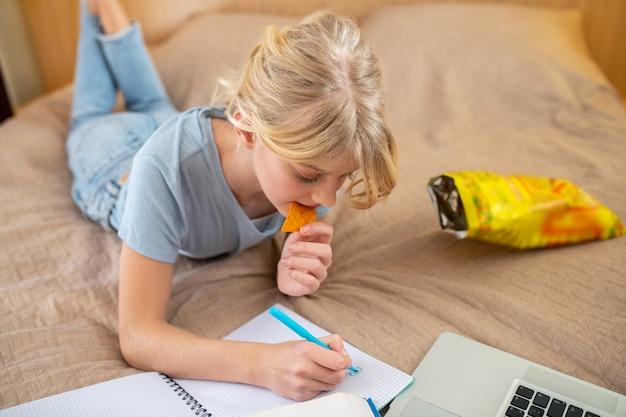 Studieren von zu hause. ein teenie-mädchen liegt auf dem bett und macht ihren unterricht