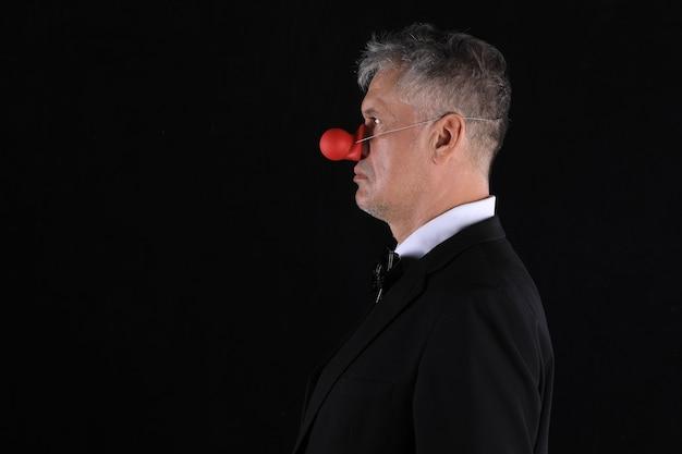 Studio dunkles porträt eines mannes mit roter nase