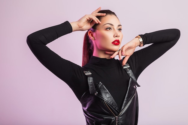 Studio frisches porträt hübsche schöne junge frau mit sexy roten lippen mit braunem haar in schwarzer modischer lederkleidung auf hellem hintergrund im zimmer. attraktives mädchenmodell, das zuhause aufwirft.