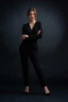 Studio frontview der jungen überzeugten frau, die schwarzen stilvollen anzug trägt und vor kamera aufwirft.