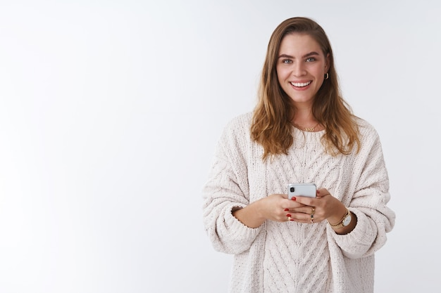 Studio gedreht charmante glücklich lächelnde frau mit smartphone suchen kamera positiv grinsend kommunikation mit app featured. bloggerin postet bild online smm, das per telefon arbeitet