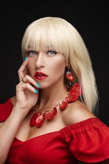 Studio-kopfschuss einer atemberaubenden jungen erwachsenen frau mit blonden haaren und schönen blauen augen, die eine modische halskette, ohrringe und ein rotes kleid mit offenen schultern trägt.