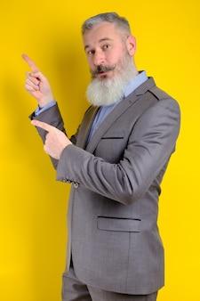 Studio porträt reifen geschäftsmann gekleidet in grauen anzug zeigt beiseite, ich wähle sie diese, gelben hintergrund