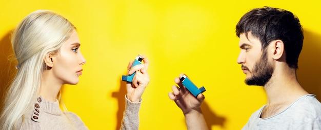 Studio-profilporträt des paares, des blonden mädchens und des brünetten kerls, die asthmatischen inhalator auf gelbem hintergrund halten.
