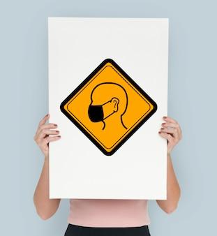 Studio shoot holding banner mit schutzmaske aufmerksamkeitszeichen