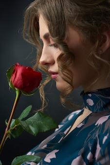 Studio sideview eines jungen schönen mädchens, das rotrose hält, näherte sich ihrem gesicht.