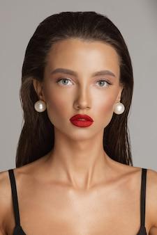 Studio stock photo porträt einer attraktiven jungen dame mit frisur und perfektem make-up, die trendige perlenohrringe mit blick in die kamera trägt. atemberaubendes modell mit leuchtend roten lippen.