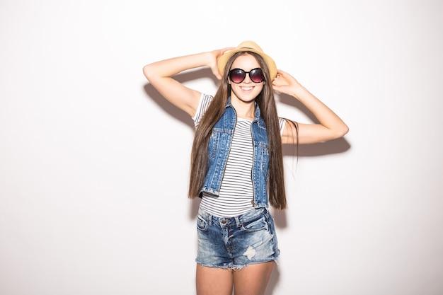 Studioansicht der fröhlichen frau mit zahnigem lächeln, trägt trendige sonnenbrille, strohhut, sommerkleid, lokalisiert über weißer wand