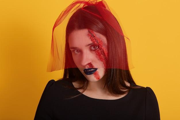 Studioaufnahme der attraktiven frau mit blutigem gesichtsschminke, dame, die lokal über gelb aufwirft