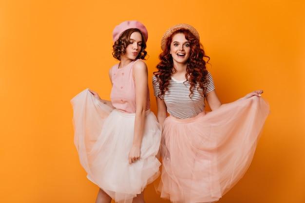 Studioaufnahme der eleganten mädchen, die spaß auf gelbem hintergrund haben. hübsche junge damen, die in röcken posieren.