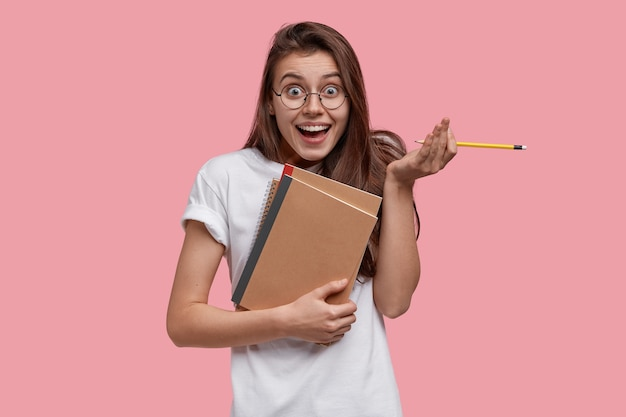 Studioaufnahme der erfreuten dunkelhaarigen frau hält bleistift, lehrbücher, sieht glücklich aus, fühlt sich froh, die arbeit zu beenden, bereitet hausaufgabe vor