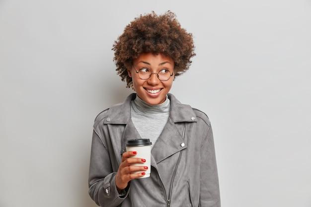 Studioaufnahme der erfreuten lächelnden afroamerikanischen frau hält pappbecher kaffee