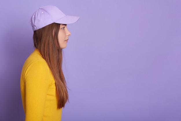Studioaufnahme der frau, die baseballmütze und gelbes hemd trägt, seitenansicht der attraktiven frau, die gerade voraus schaut