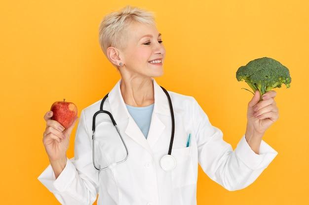 Studioaufnahme der freundlichen positiven blonden reifen ärztin, die isoliert mit frischem brokkoli und apfel in ihren händen aufwirft und rät, mehr gemüse und obst zu essen. gesundes essen, diät und ernährung
