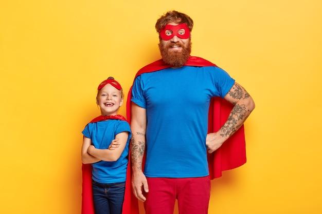 Studioaufnahme der fröhlichen familie in superheldenanzügen
