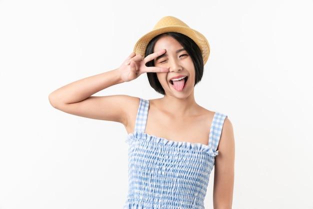 Studioaufnahme der fröhlichen schönen asiatischen frau im blauen farbkleid und im tragen eines hutes und des stehens auf weißem hintergrund.
