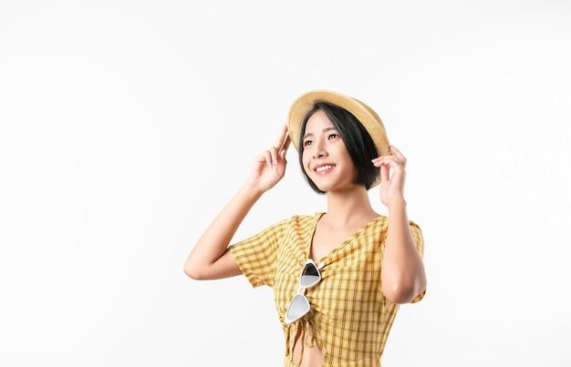 Studioaufnahme der fröhlichen schönen asiatischen frau im gelben farbkleid und im tragen eines hutes und des stehens auf weißem hintergrund.