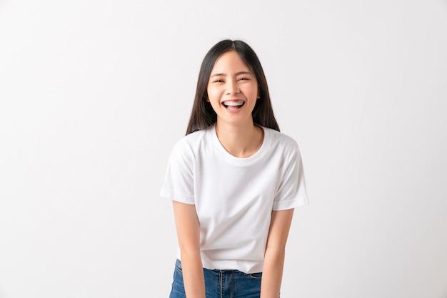 Studioaufnahme der fröhlichen schönen asiatischen frau im weißen t-shirt und im stand auf weißer wand.