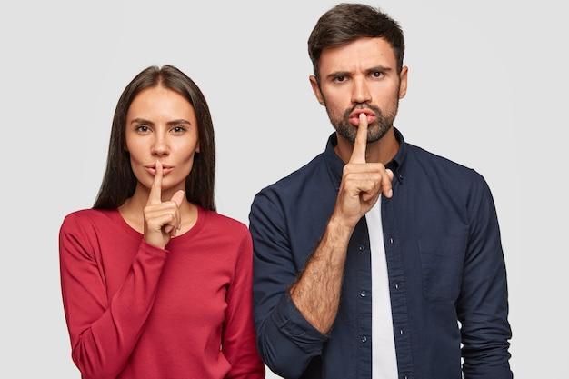 Studioaufnahme der geheimen jungen kaukasischen frau und des mannes halten zeigefinger auf den lippen, stehen nebeneinander