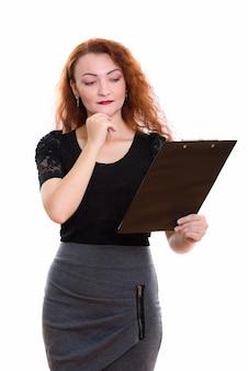 Studioaufnahme der geschäftsfrau, die auf zwischenablage liest, während lokalisiert gegen weißen hintergrund gedacht wird