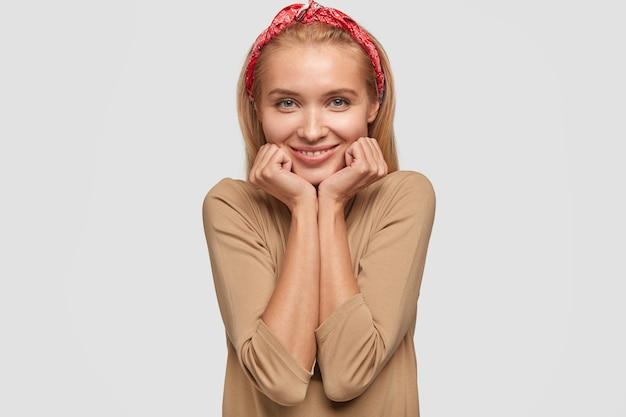 Studioaufnahme der glücklichen blonden jungen frau, die gegen die weiße wand aufwirft