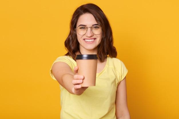 Studioaufnahme der glücklichen kaukasischen frau hält tasse kaffee oder tee wegnehmen