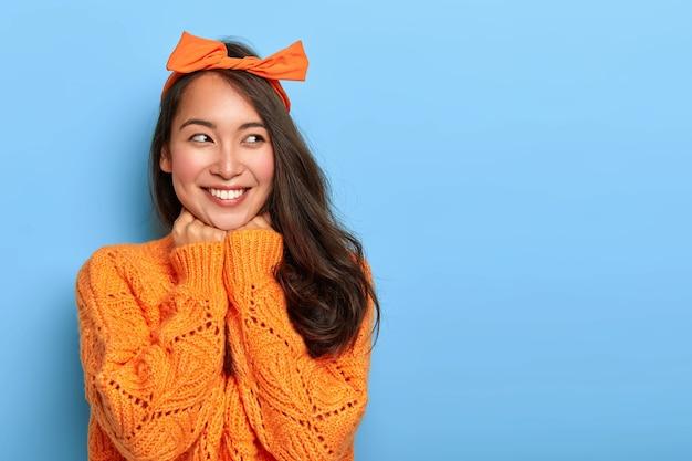 Studioaufnahme der glücklichen optimistischen frau trägt leuchtend orange gestrickten pullover, schleifenstirnband, hält hände unter kinn