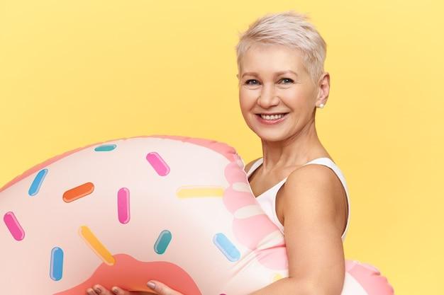 Studioaufnahme der glücklichen positiven reifen kaukasischen frau mit pixie-frisur, die aufblasbaren kreis in form des rosa donuts trägt, während der sommerferien im see oder im meer schwimmt und freudig lächelt