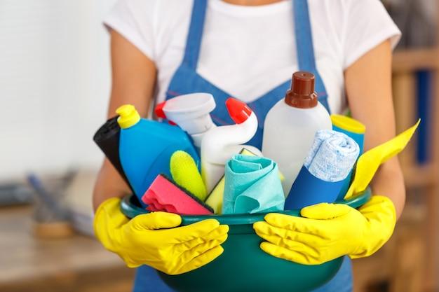 Studioaufnahme der haushälterin beim putzen des büros. frau, die handschuhe trägt und eine schüssel voller flaschen mit desinfektionsmittel hält